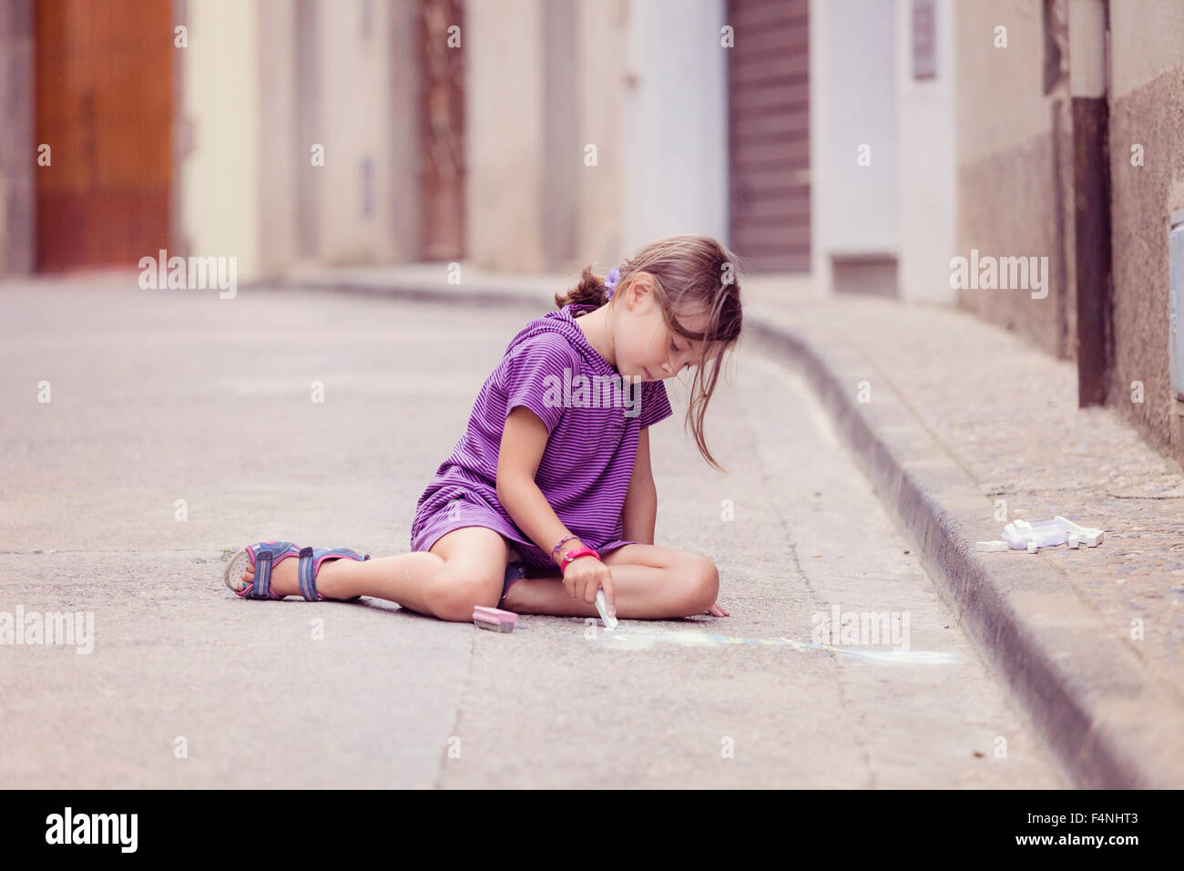 Little girl drawing with crayon on the street - Stock Image