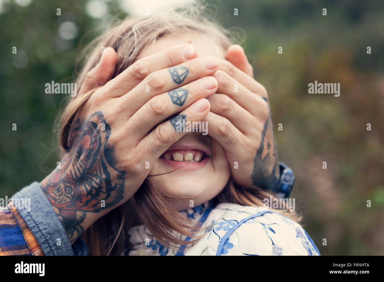 Man's tattooed hands covering eyes of his daughter - Stock Image