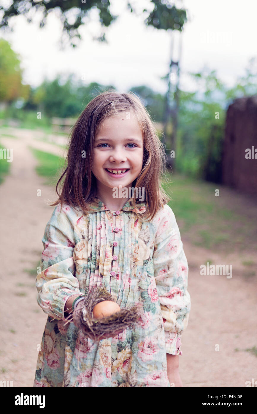 Smiling girl holding an egg in a nest Stock Photo