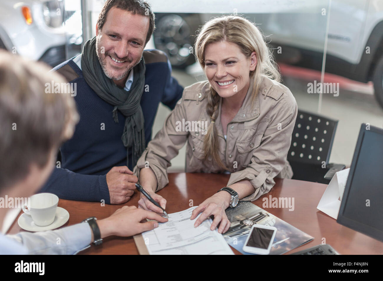 Couple signing sales contract at car dealership - Stock Image