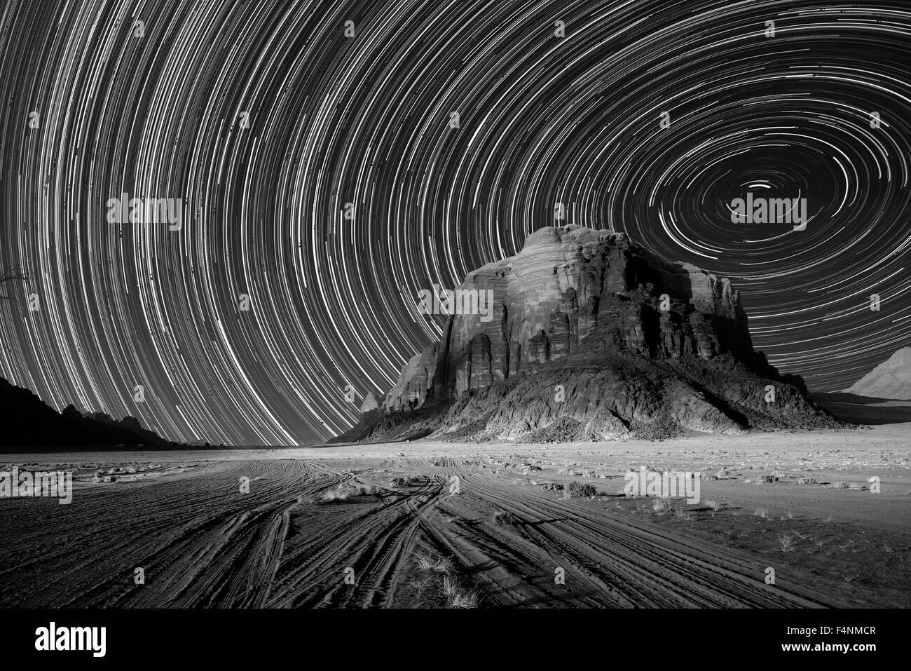 Desert scene with star trails and sand stone mountain - Stock Image