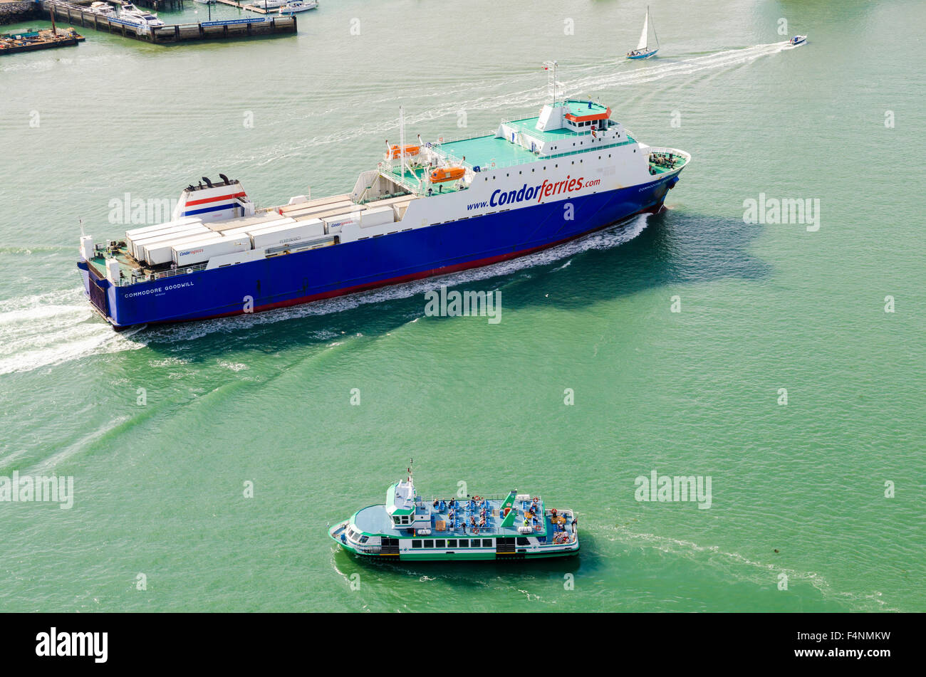 Condor Ferries freight ferry Commodore Goodwill and a passenger boat passing in Portsmouth Harbour, Hampshire, England. - Stock Image