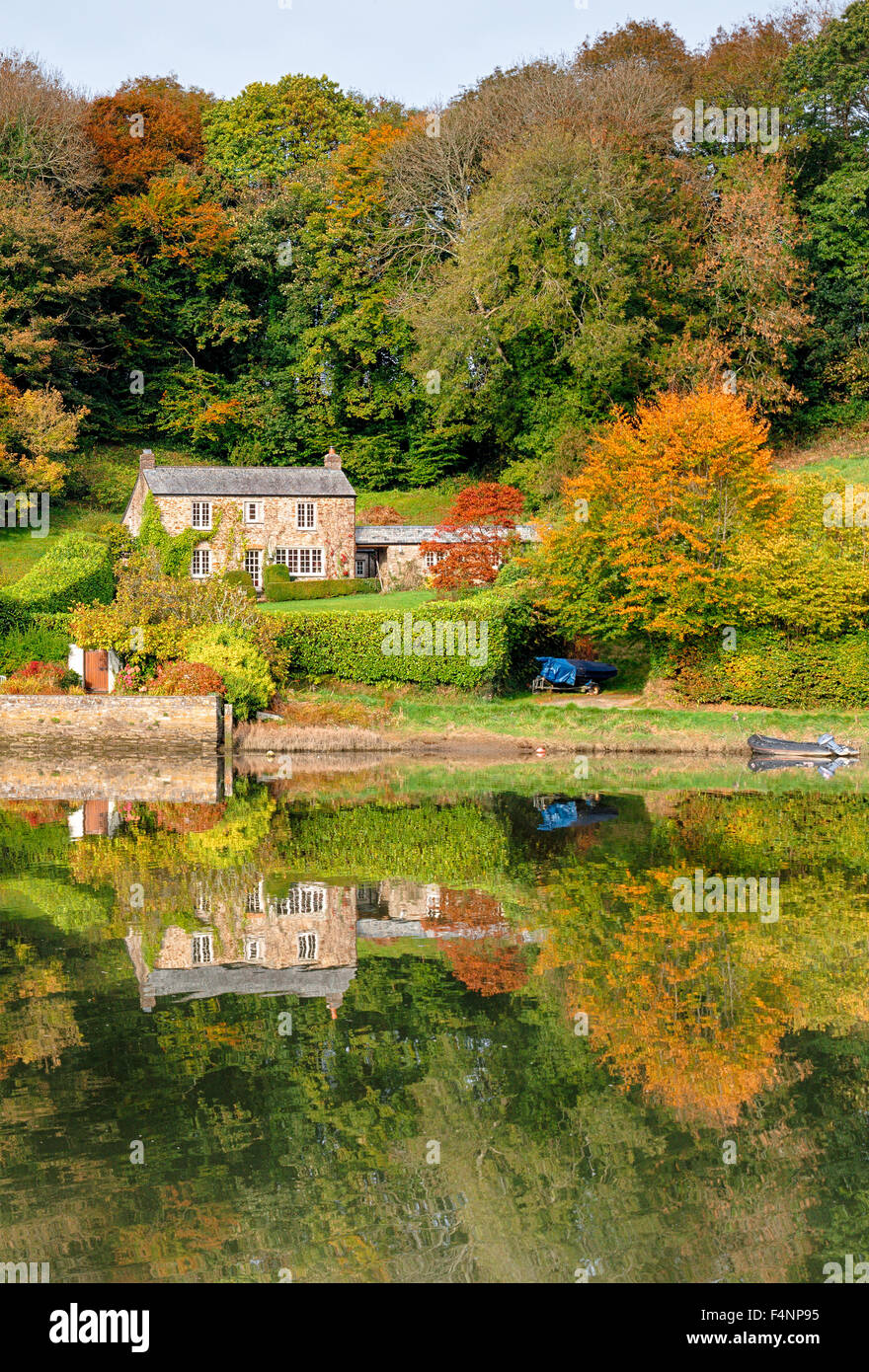 A Beautiful Cottage Surrounded By Autumn Colour And Reflected In Lake
