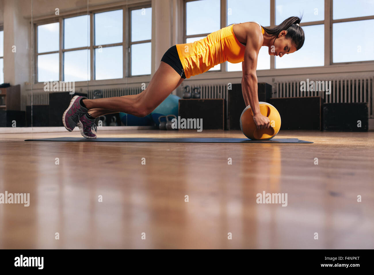 Fit young female athlete working out on her core muscles. Muscular woman exercising on fitness mat doing push ups - Stock Image