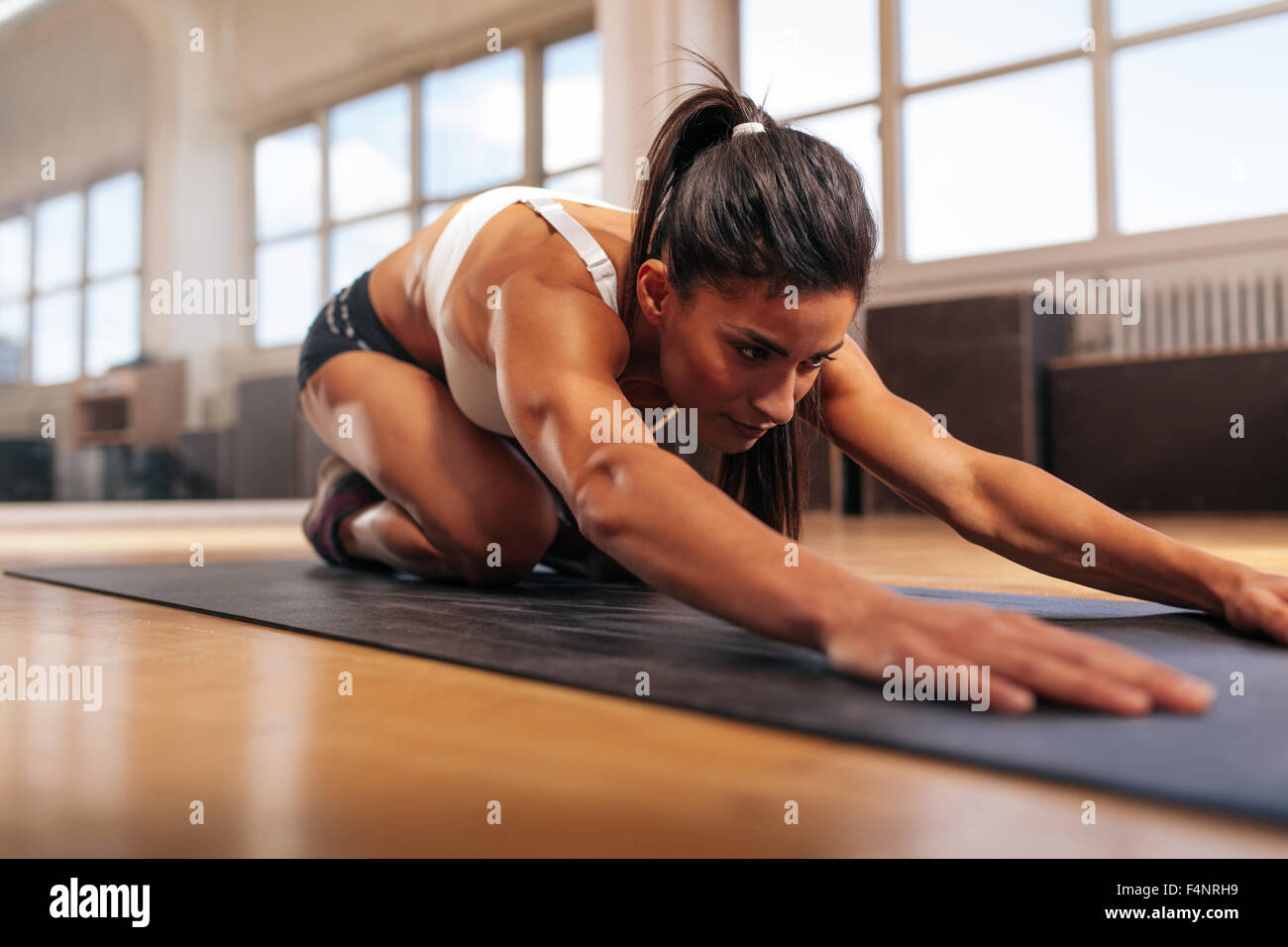 Young muscular woman doing stretching workout on fitness mat. Female performing yoga at gym. - Stock Image