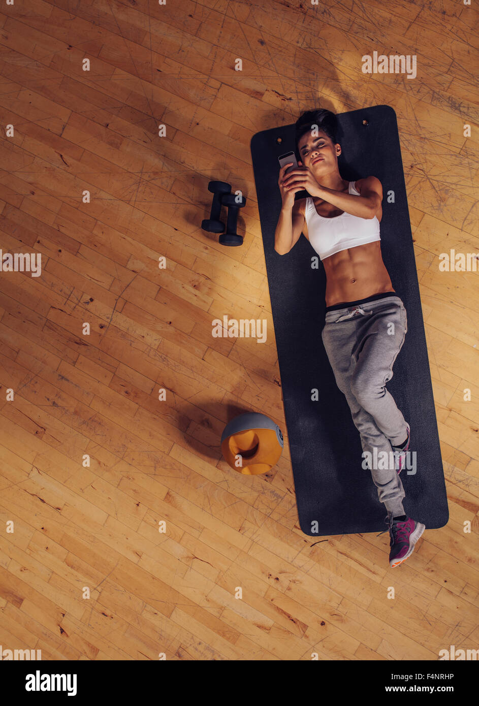 Overhead view of fitness woman lying on mat using mobile phone. Top view of young female taking break from exercise. - Stock Image