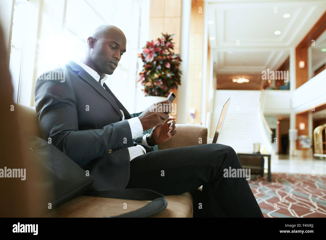 Male executive sitting on sofa looking at his mobile phone. African businessman waiting in hotel lobby. - Stock Image