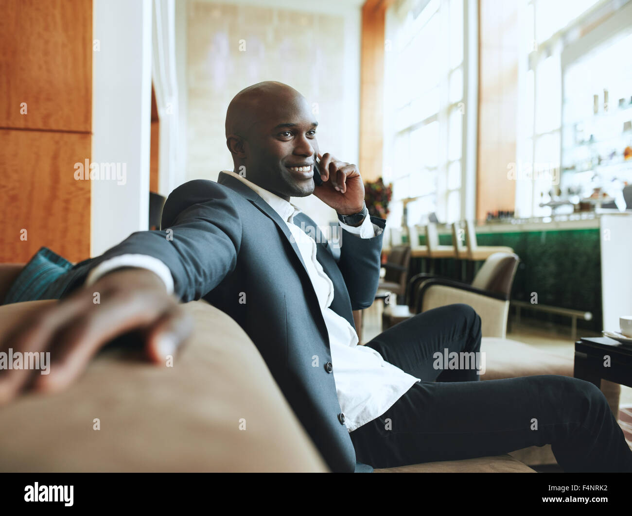 Happy young businessman sitting relaxed on sofa at hotel lobby making a phone call, waiting for someone. - Stock Image