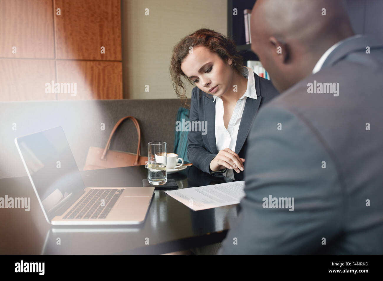 Serious business people working together in a cafe and reading some contract documents. Businessman and businesswoman - Stock Image