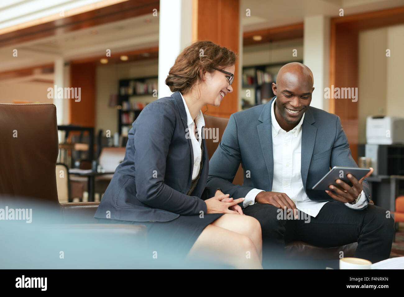 Shot of two people looking at something on a touchscreen computer. Smiling business people using digital tablet - Stock Image