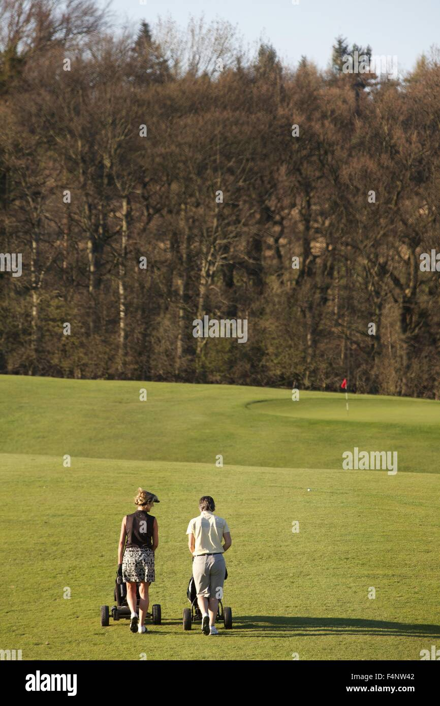 Two female club golfers walking with golf clubs and there trolleys down a fairway at an English golf club in the - Stock Image