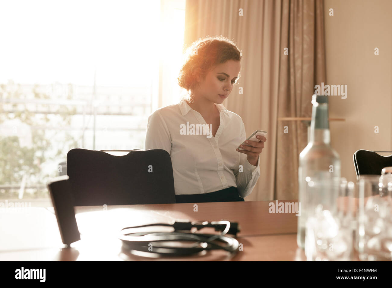Image of businesswoman at conference table reading text message on her mobile phone. Caucasian female executive - Stock Image