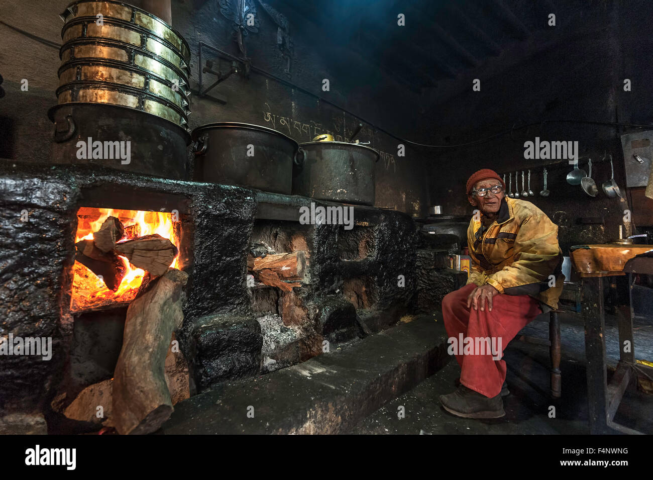 Old Monk is sitting in kitchen next to the fire. - Stock Image