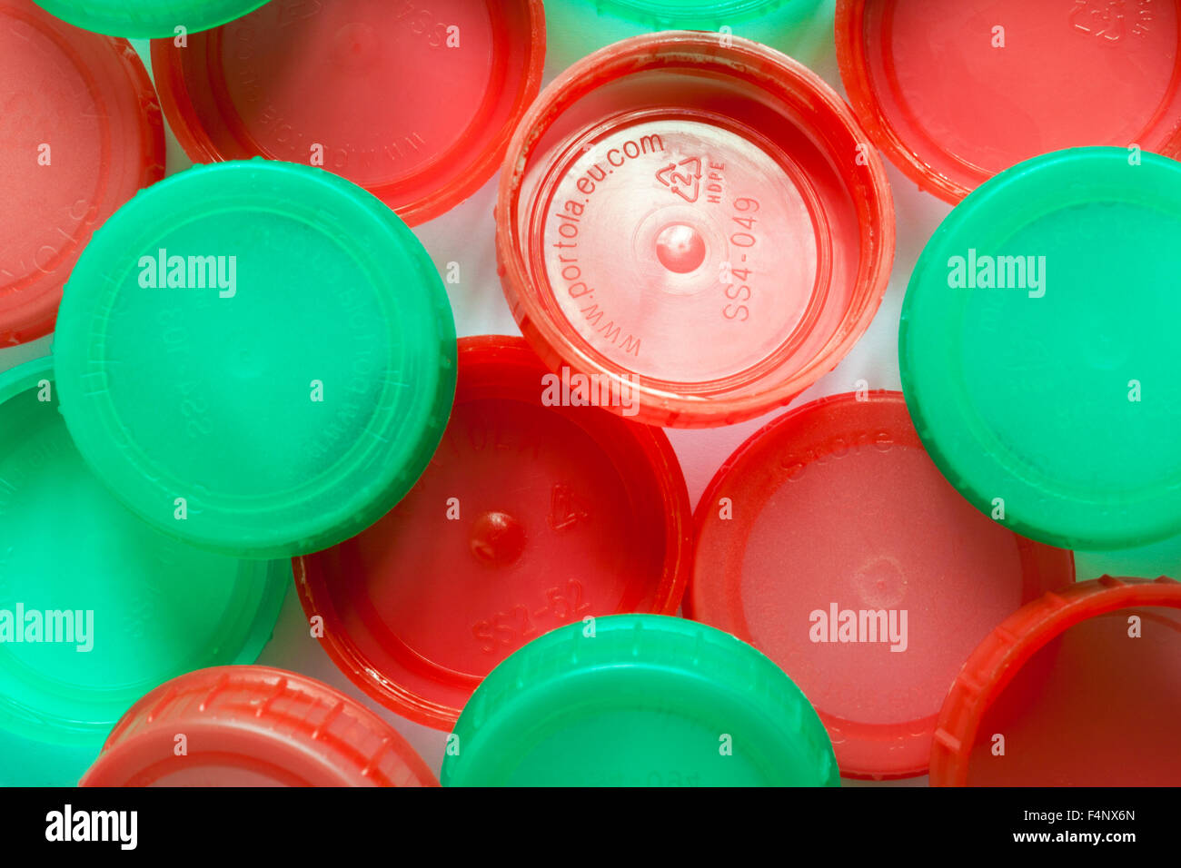 red and green plastic milk bottle tops - Stock Image