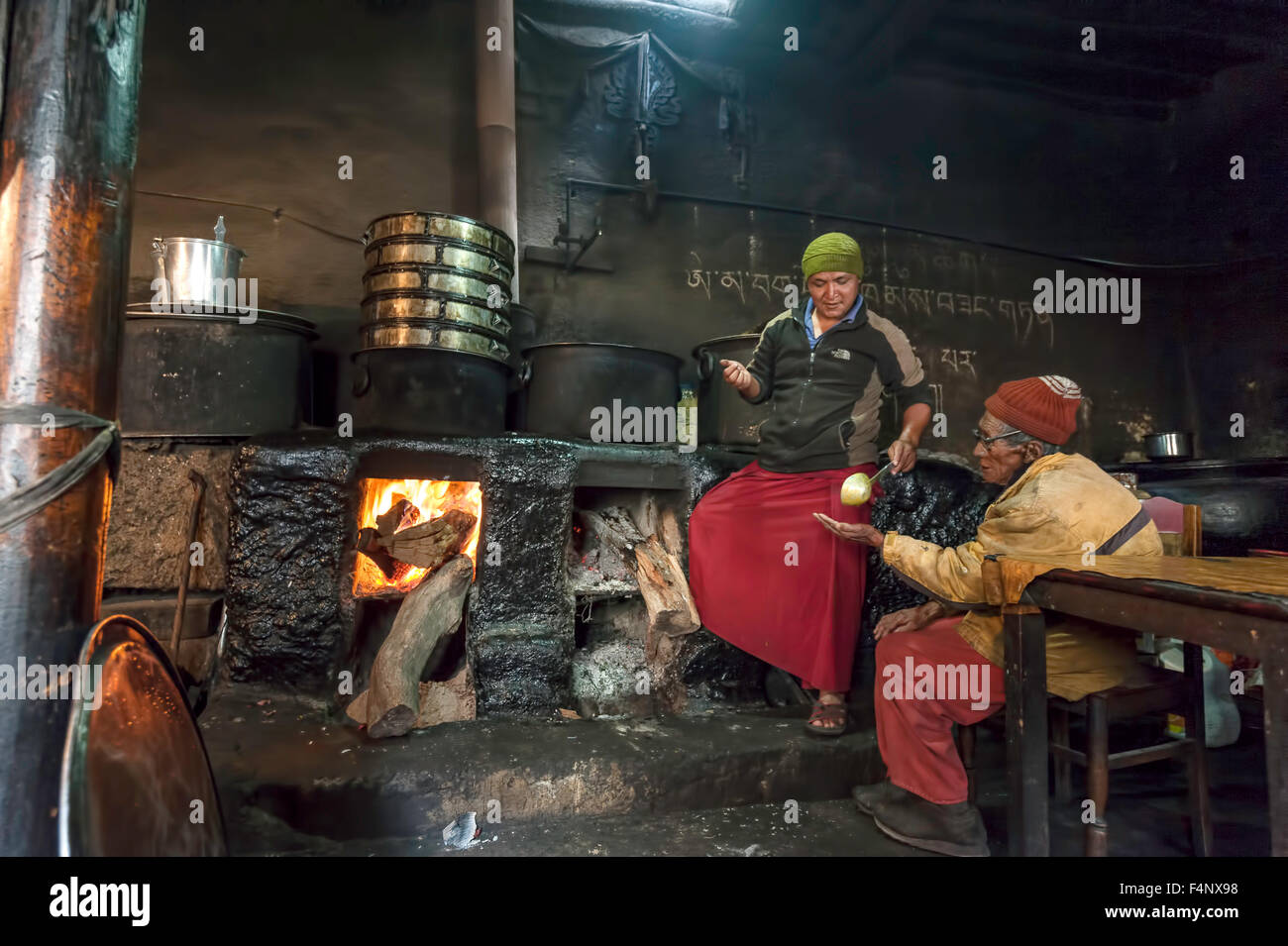 Old Monk is sitting in kitchen next to the fire and cook is serving him food - Stock Image