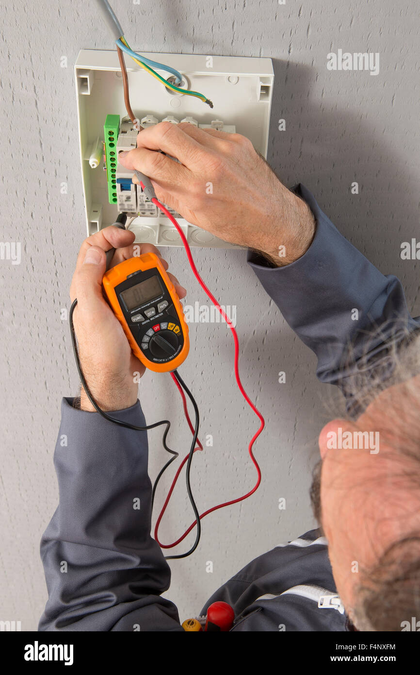 Hand of an electrician with multimeter probe at an electrical switchgear - Stock Image