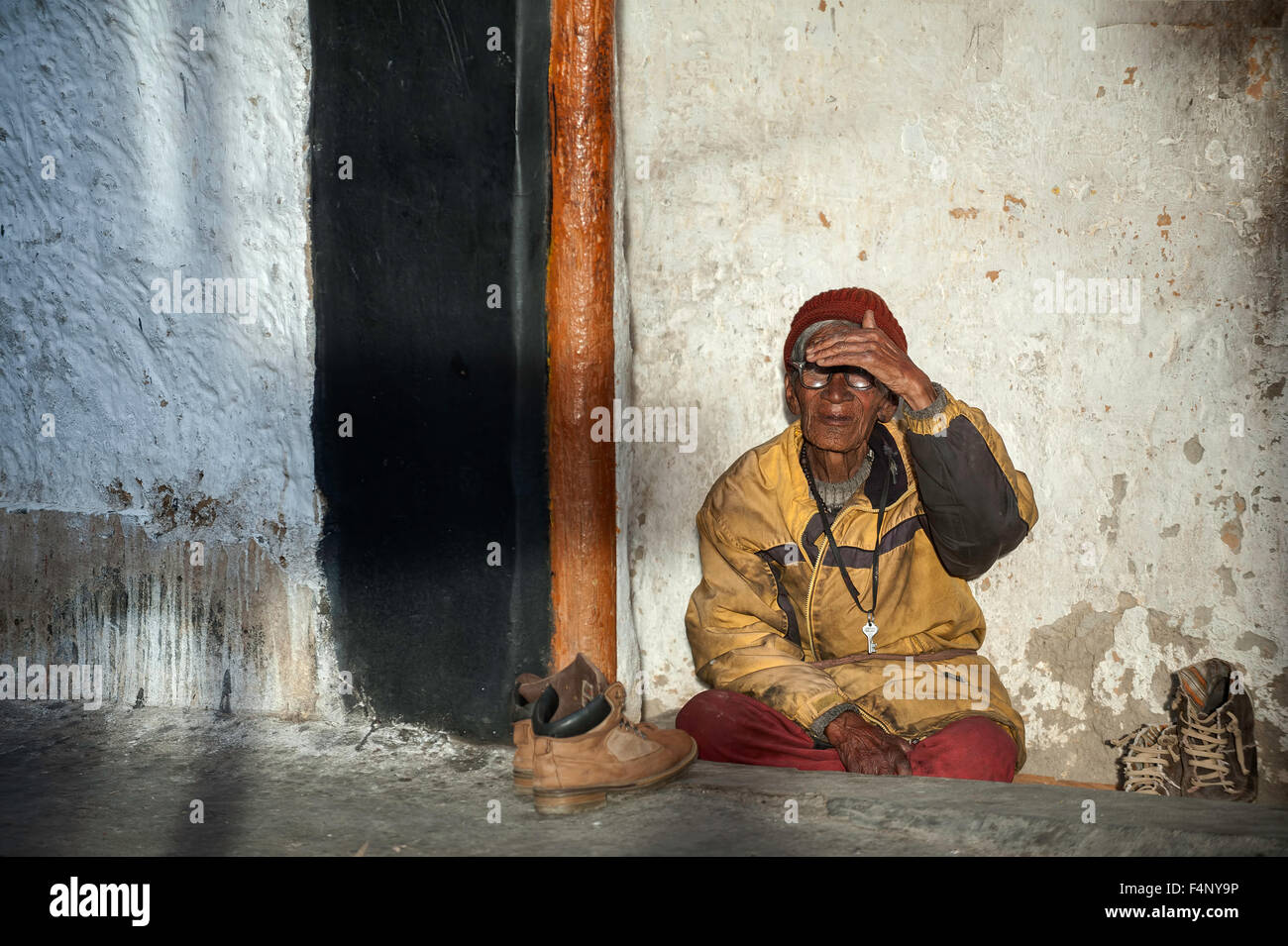 Old Monk is relaxing outside monastery - Stock Image