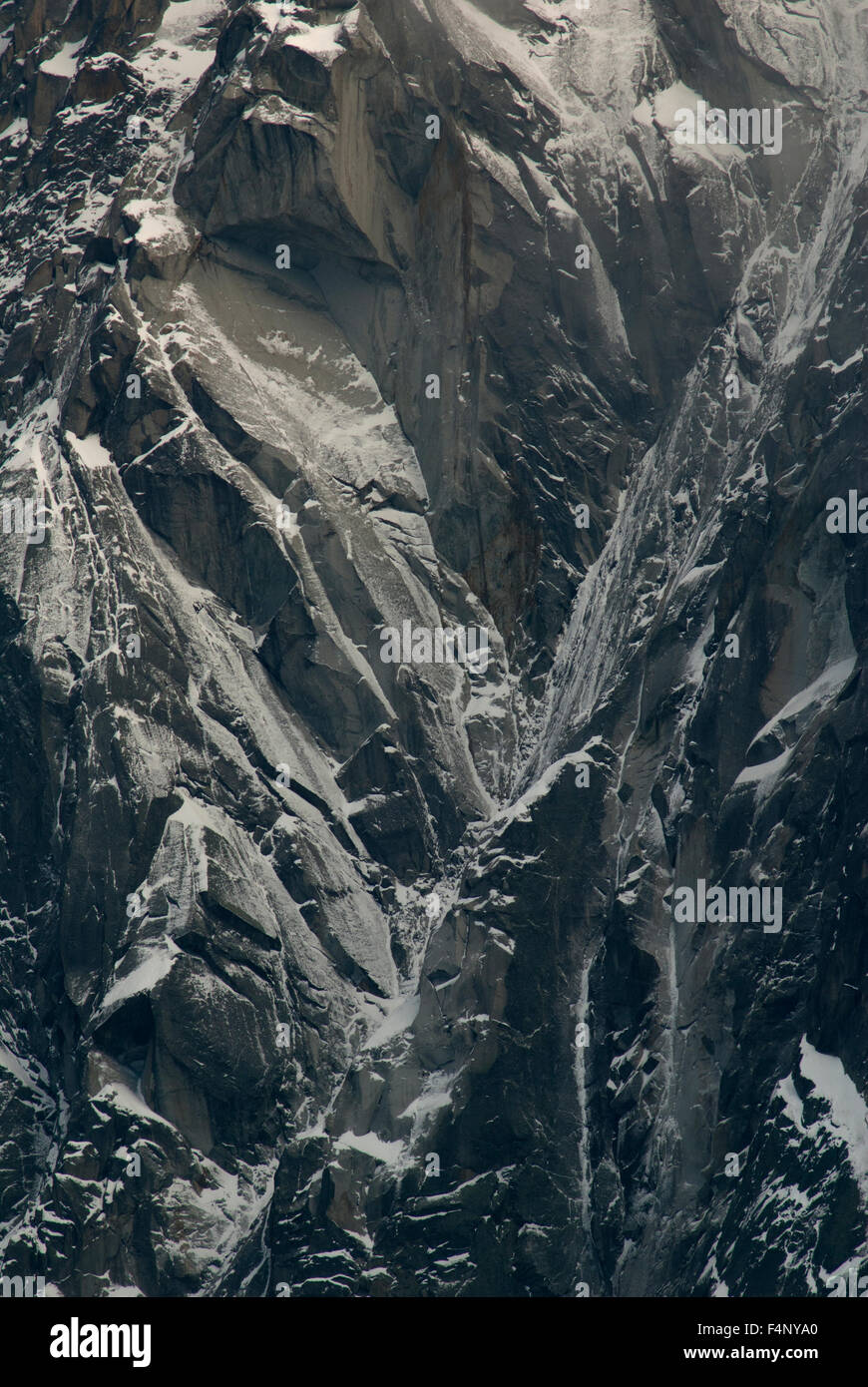 Close up of rock face dusted with snow - Stock Image