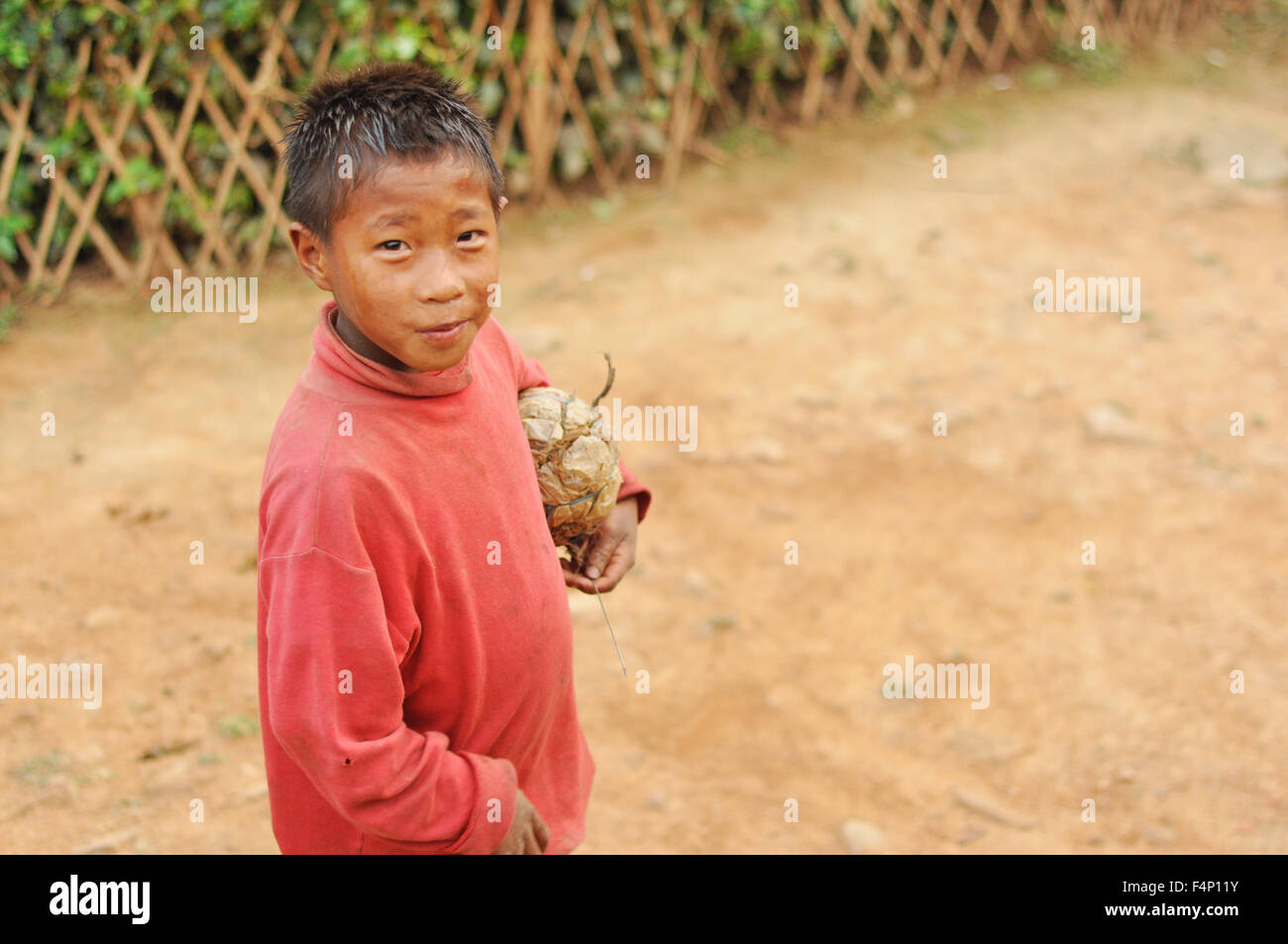 Nagaland, India - March 2012: Small footballer with hand-made ball in Nagaland, remote region of India. Documentary - Stock Image