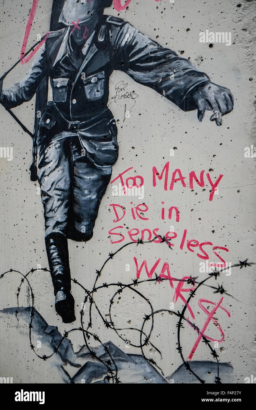 Political showing a soldier escaping The Berlin Wall. Seen close to the Holocaust memorial in Berlin, Germany. - Stock Image