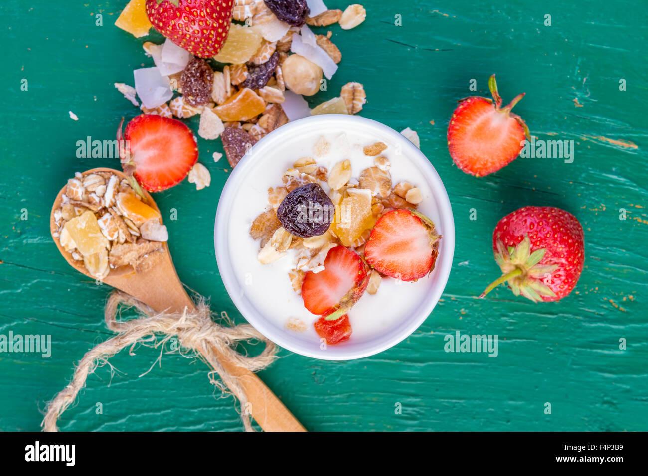 Yogurt with cereals muesli, fresh strawberries, banana and raisins in bowl on wooden background - Stock Image