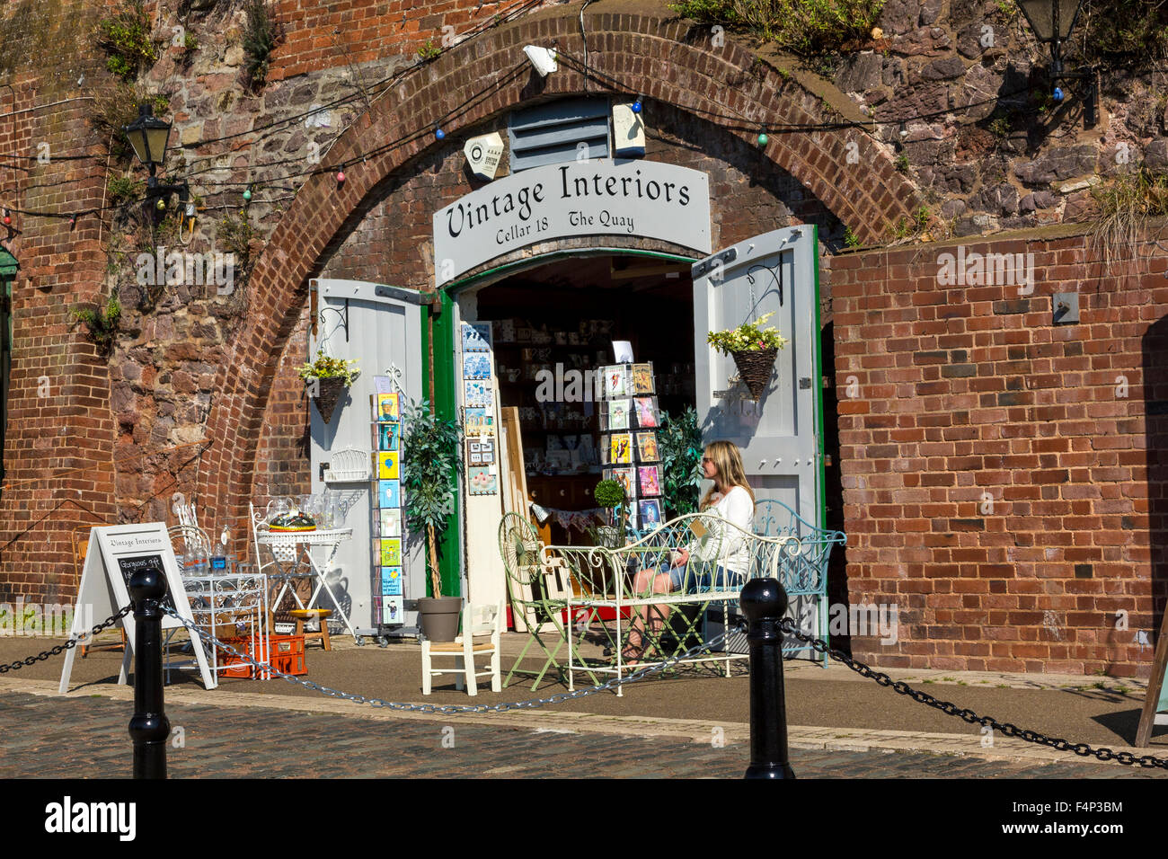 A Quiet, Sunny Moment for an Independent Shopkeeper in the Historic Old Cellars, Exeter Quay, Devon. - Stock Image