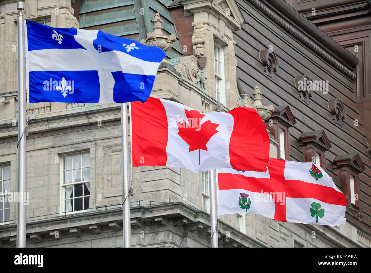 Quebec, Canadian and Montreal flags waving with the foreground of City Hall of Montreal, Quebec, Canada - Stock Image