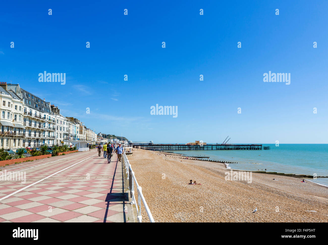 The seafront promenade and beach with the burnt out pier in the distance, Hastings, East Sussex, England, UK - Stock Image