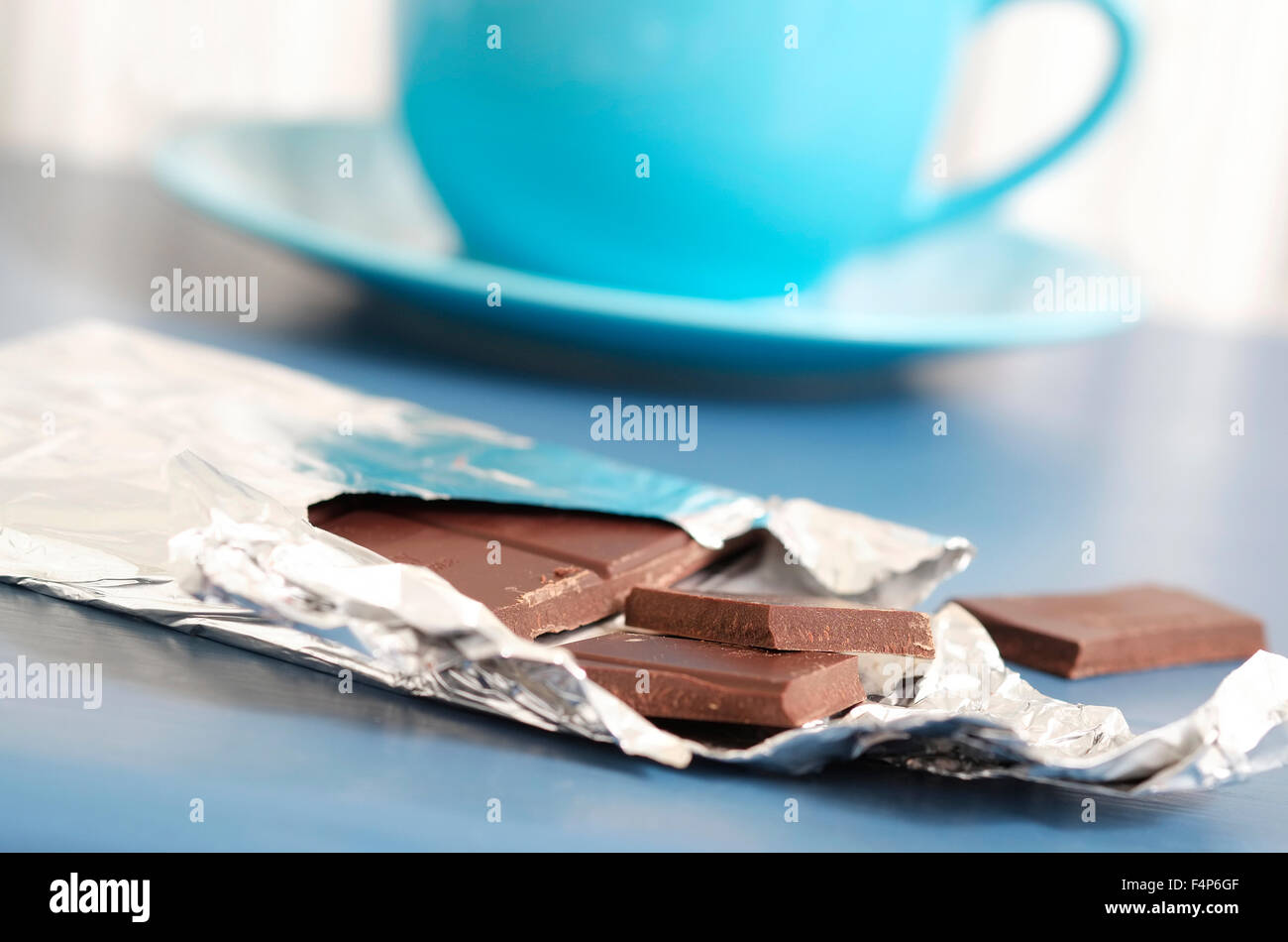 bar of dark chocolate on blue table top - Stock Image