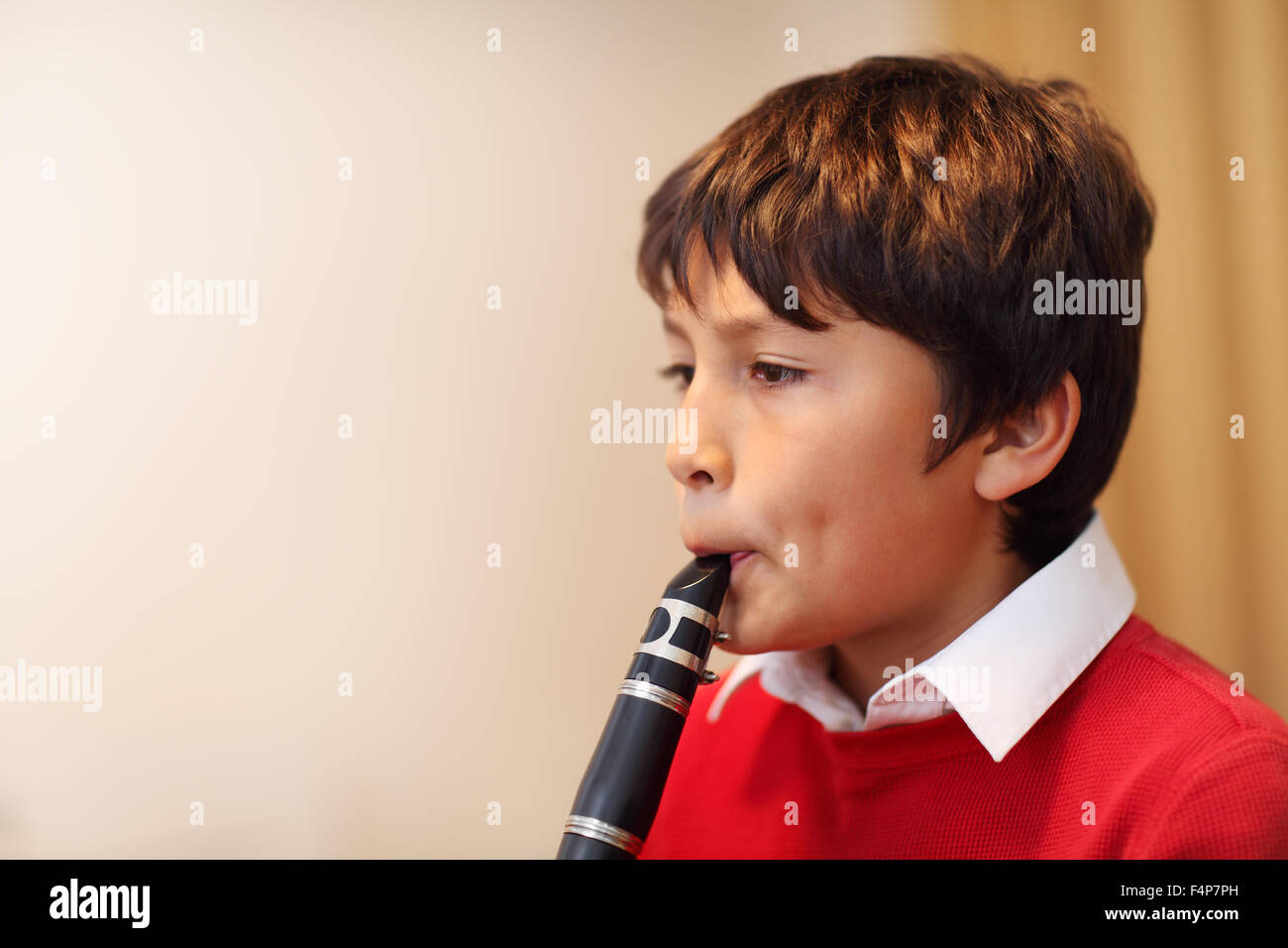 Young boy playing the clarinet - shallow depth of field - warm tones. Copy space - Stock Image