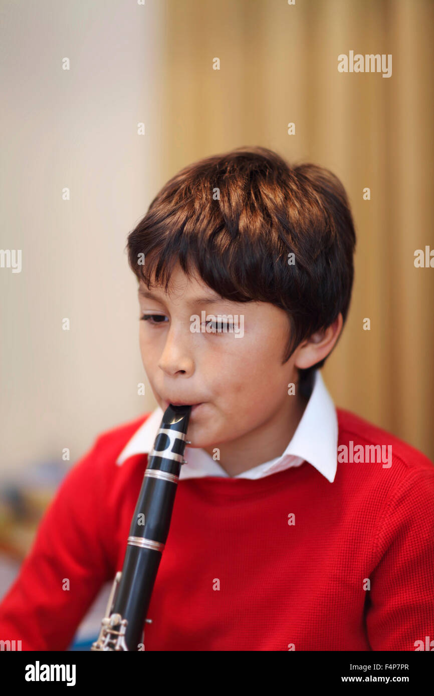 Young boy playing the clarinet - shallow depth of field - warm tones. Portrait layout. Copy space top. - Stock Image