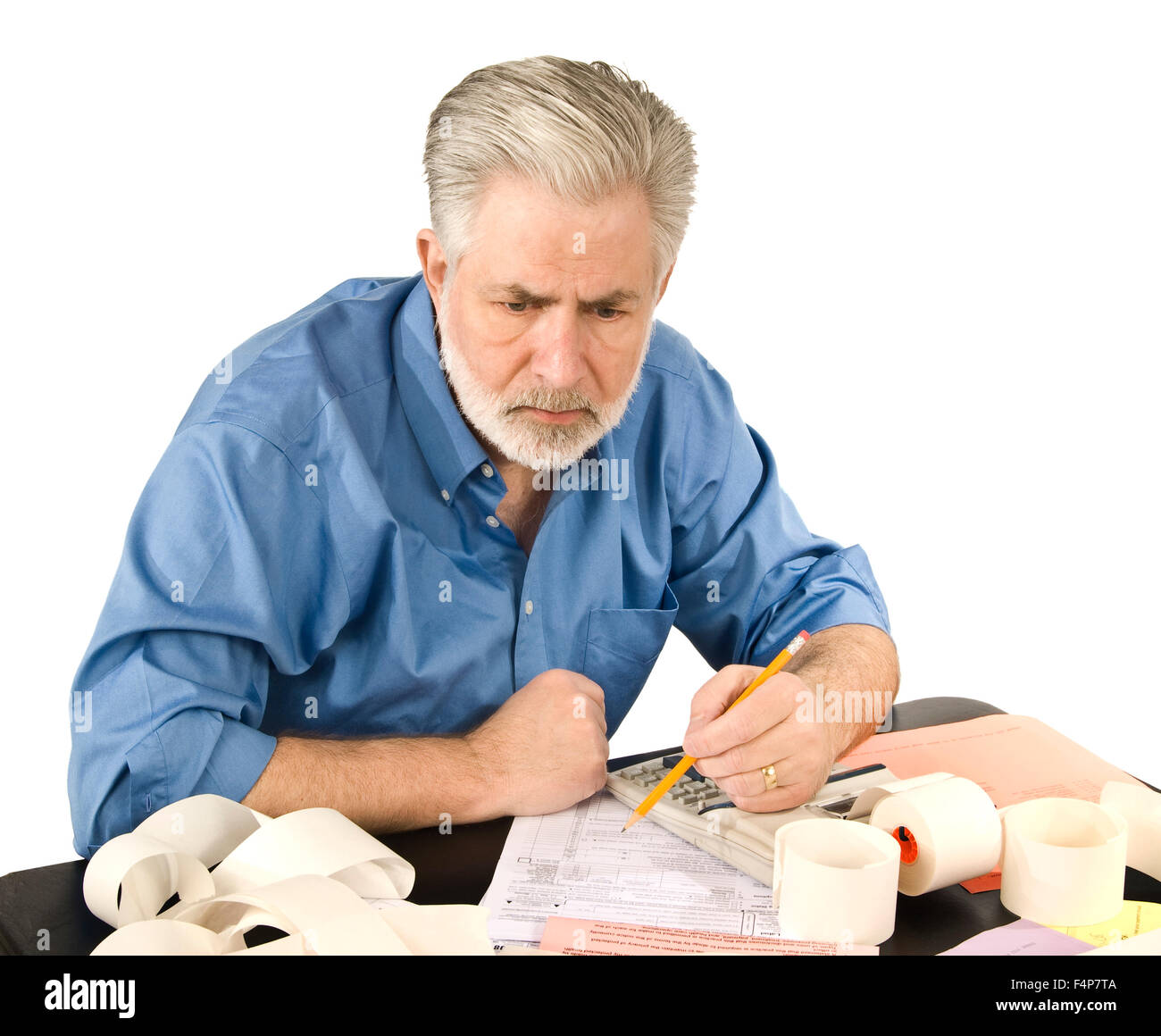 A mature man is working on his taxes - Stock Image