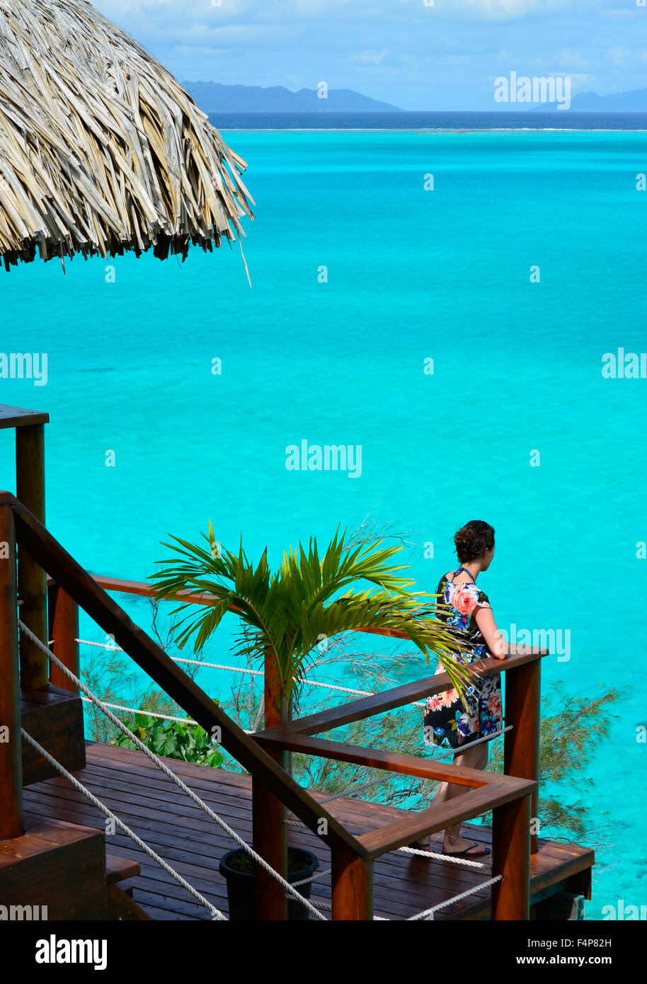 Female tourist on the balcony of an overwater bungalow with thatched roof in a luxury resort looking over the Bora - Stock Image