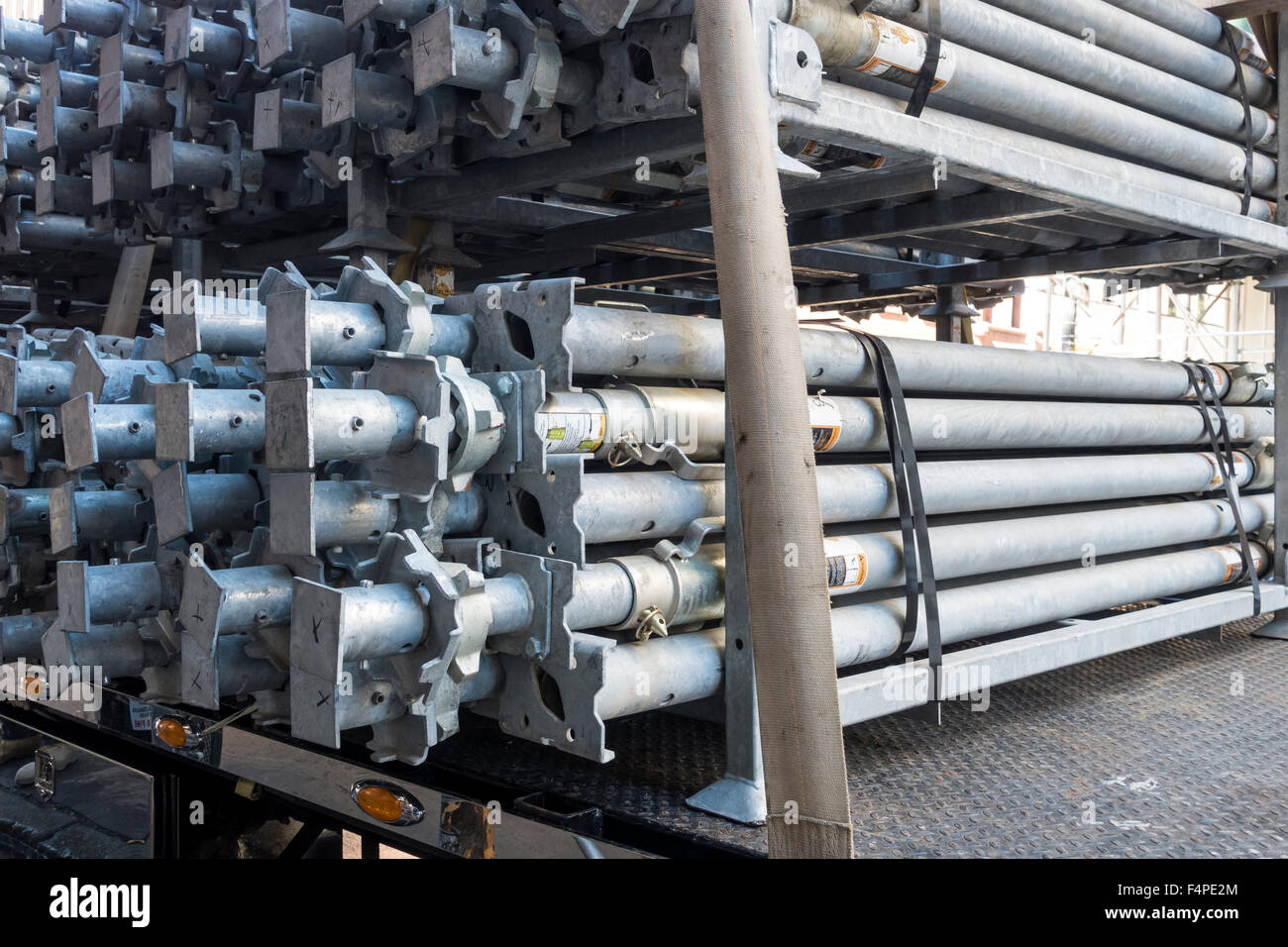 Tubular steel adjustable length props on a truck near a building site - Stock Image