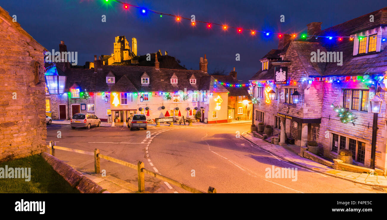 View of the lit-up ruin of Corfe Castle in Dorset, UK with Christmas lights decorating the village below. - Stock Image