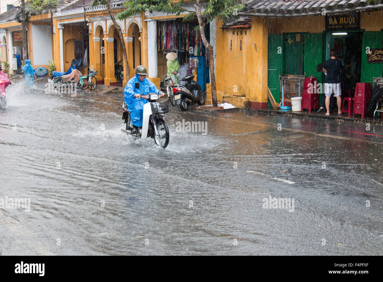 Hoi An ancient town Vietnam, biker on scooter motorcycle rides through flooded road during thunderstorms,Vietnam - Stock Image