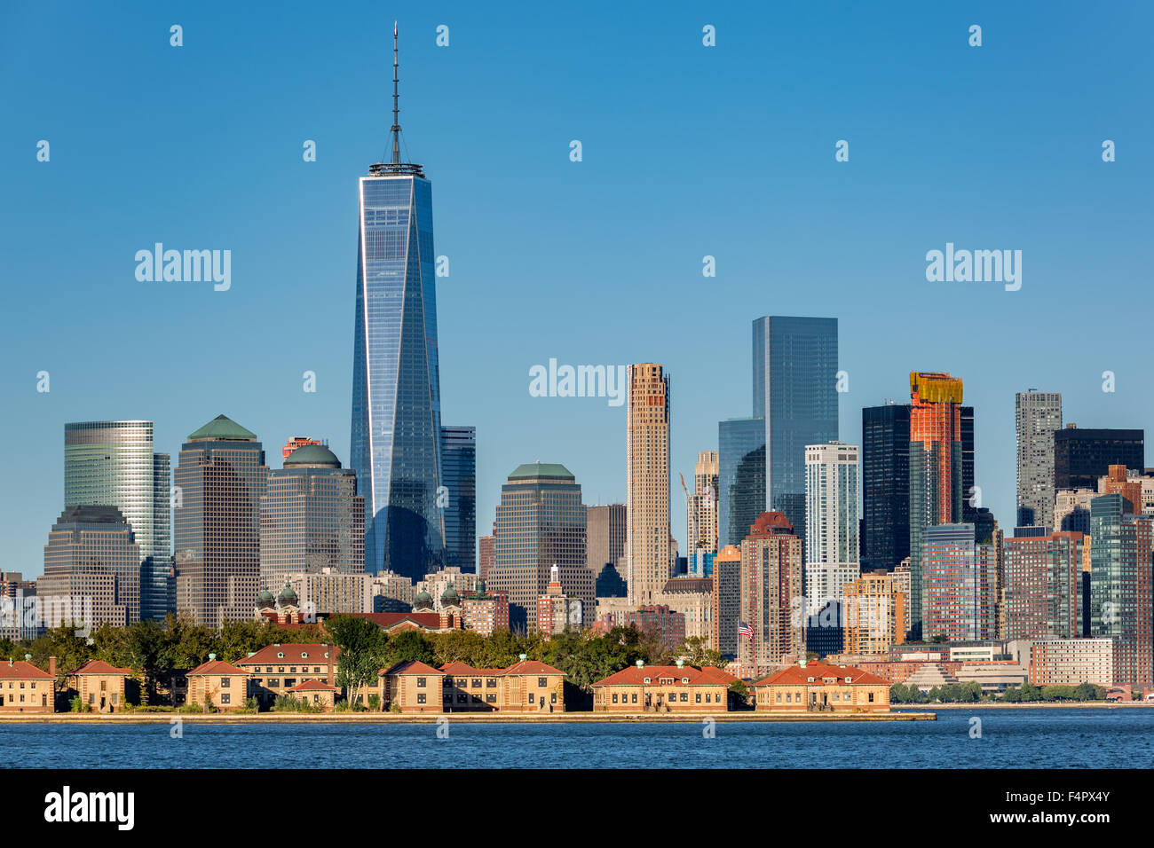 Downtown New York skyline with Ellis Island in the foreground - Stock Image