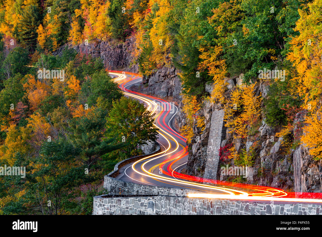 Traffic light trails on Hawk's Nest winding road (route 97) in Upstate New York, on an autumn evening. - Stock Image