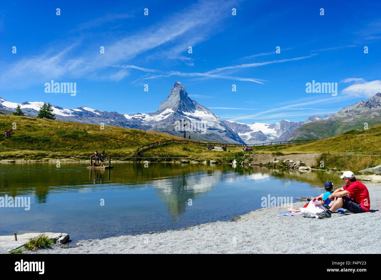 People relaxing by the lake under Matterhorn peak in summer. July, 2015. Matterhorn, Switzerland. - Stock Image