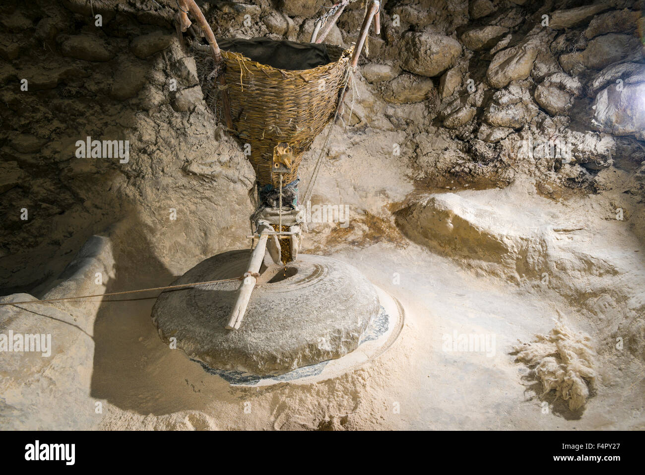 A simple grain mill is used by the local farmers - Stock Image