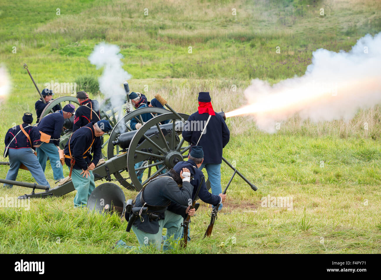 Unidentifiable union soldiers fire a cannon during a reenactment of the Civil War Battle of Gettysburg. - Stock Image