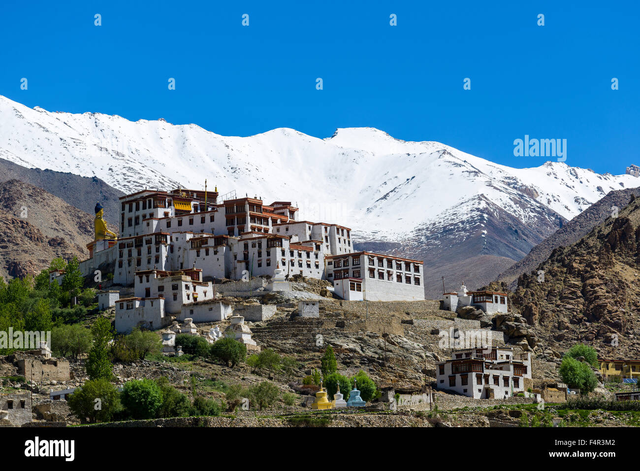 The Buildings of Likir Gompa, a monastery located on a hill in barren landscape, snow covered mountains in the distance - Stock Image