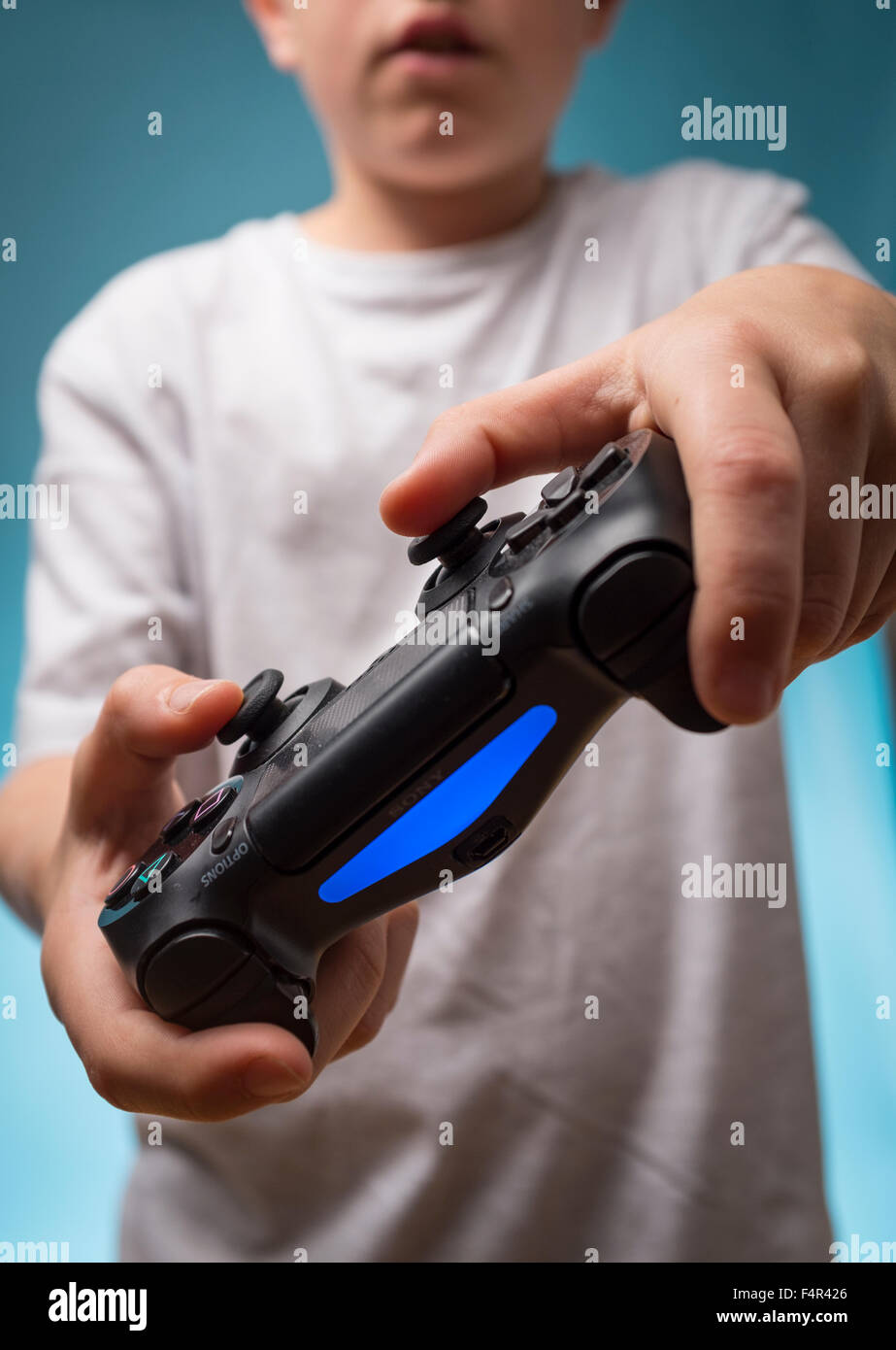 A child playing computer games with a PS4 Playstation four controller - Stock Image