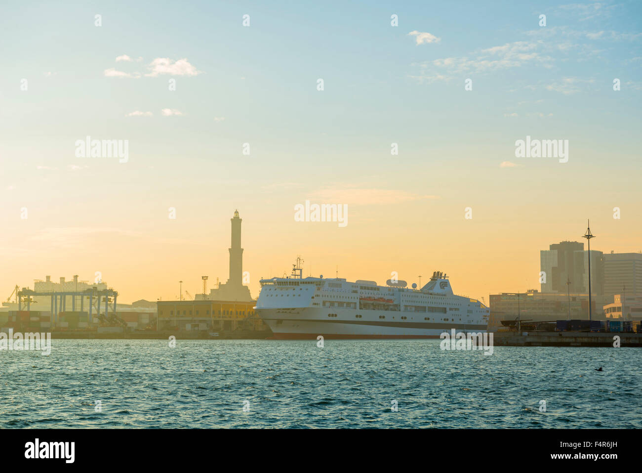 Port with passenger ship and lighthouse in sunset in Genoa, Italy. - Stock Image