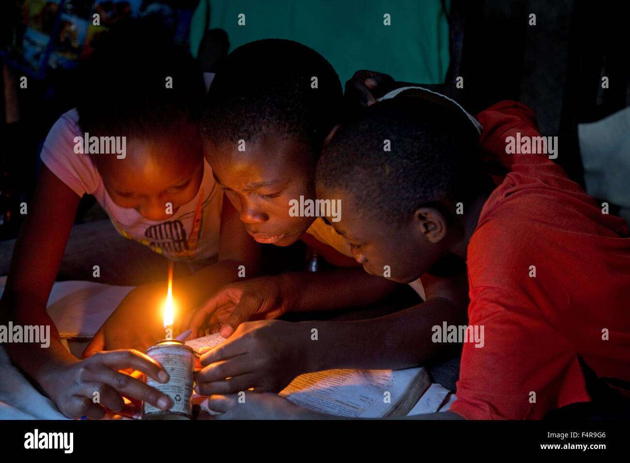 African children trying to read book with home made kerosene light Kamere Lake Naivasha Kenya - Stock Image