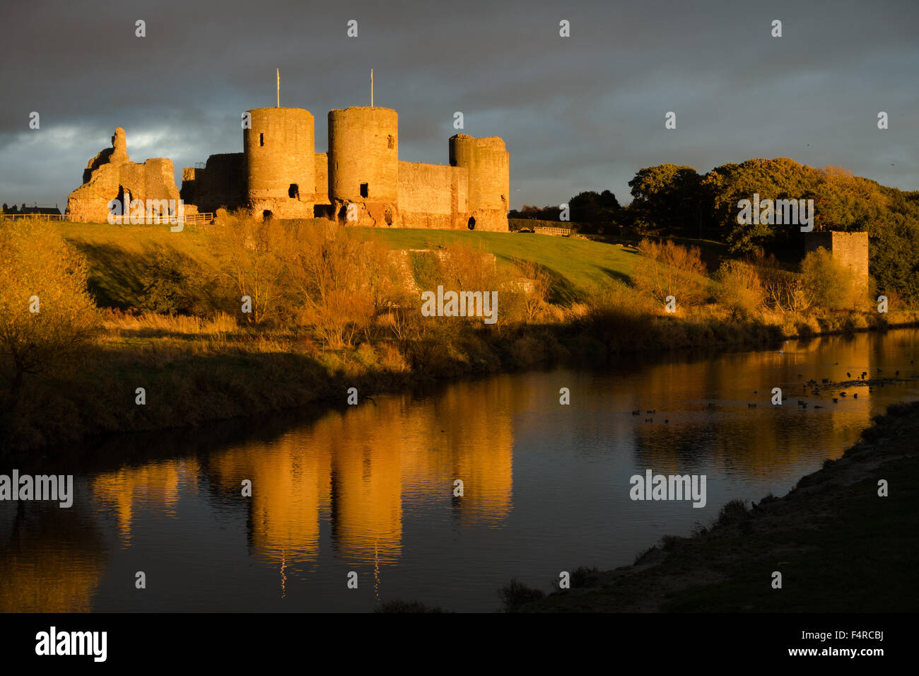 Rhuddlan castle at sunset, with storm clouds behind and reflection in the Clwyd River - Stock Image