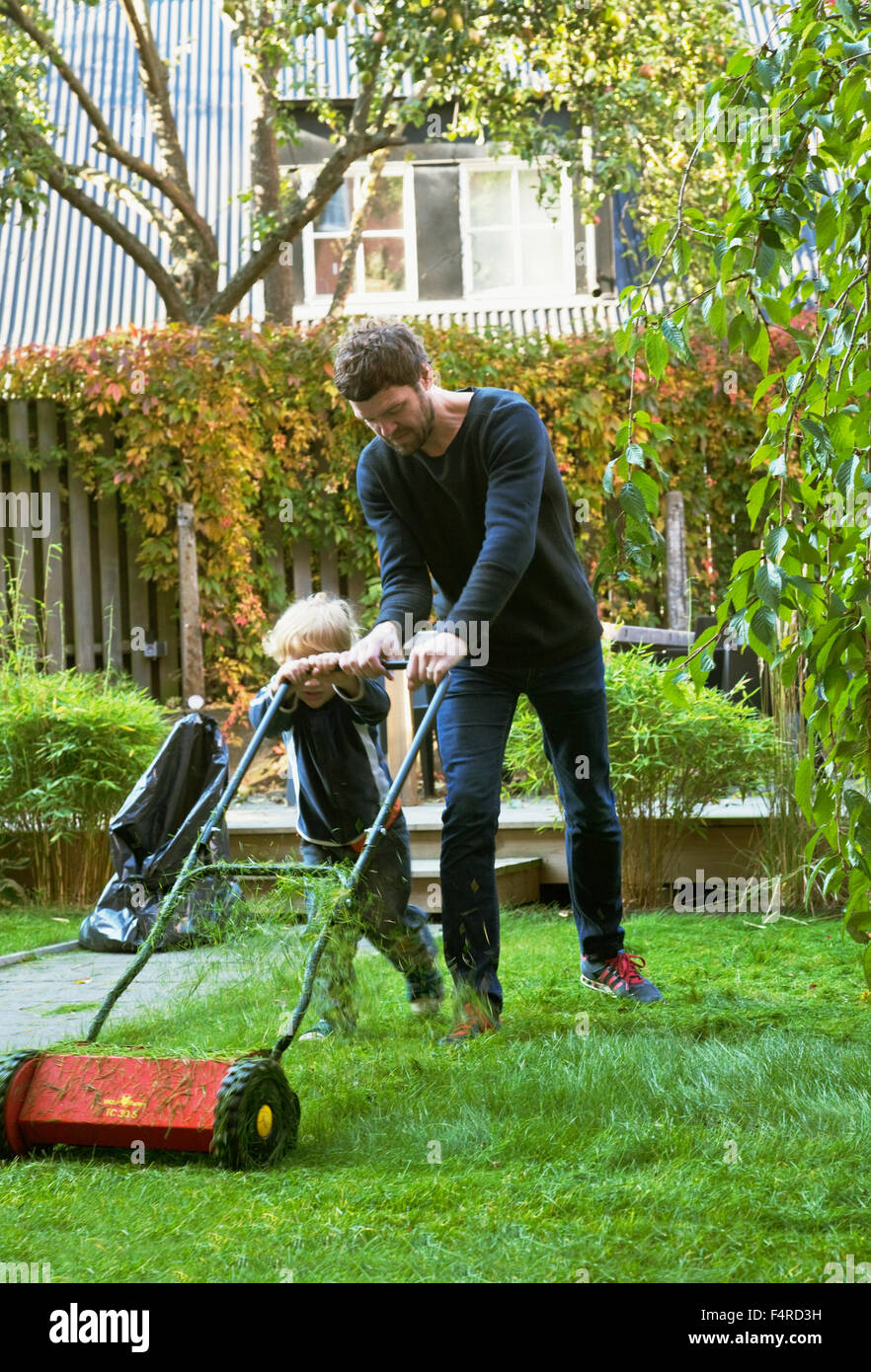 Sweden, Skane, Osterlen, Borrby, Father and son (4-5) mowing lawn in domestic garden - Stock Image