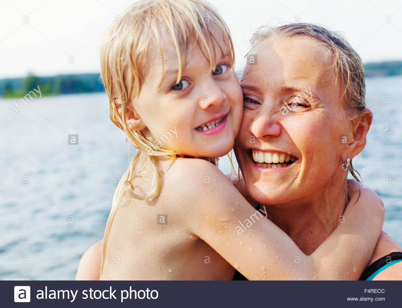 Sweden, Uppland, Varmdo, Portrait of mother with son (4-5) swimming in lake - Stock Image