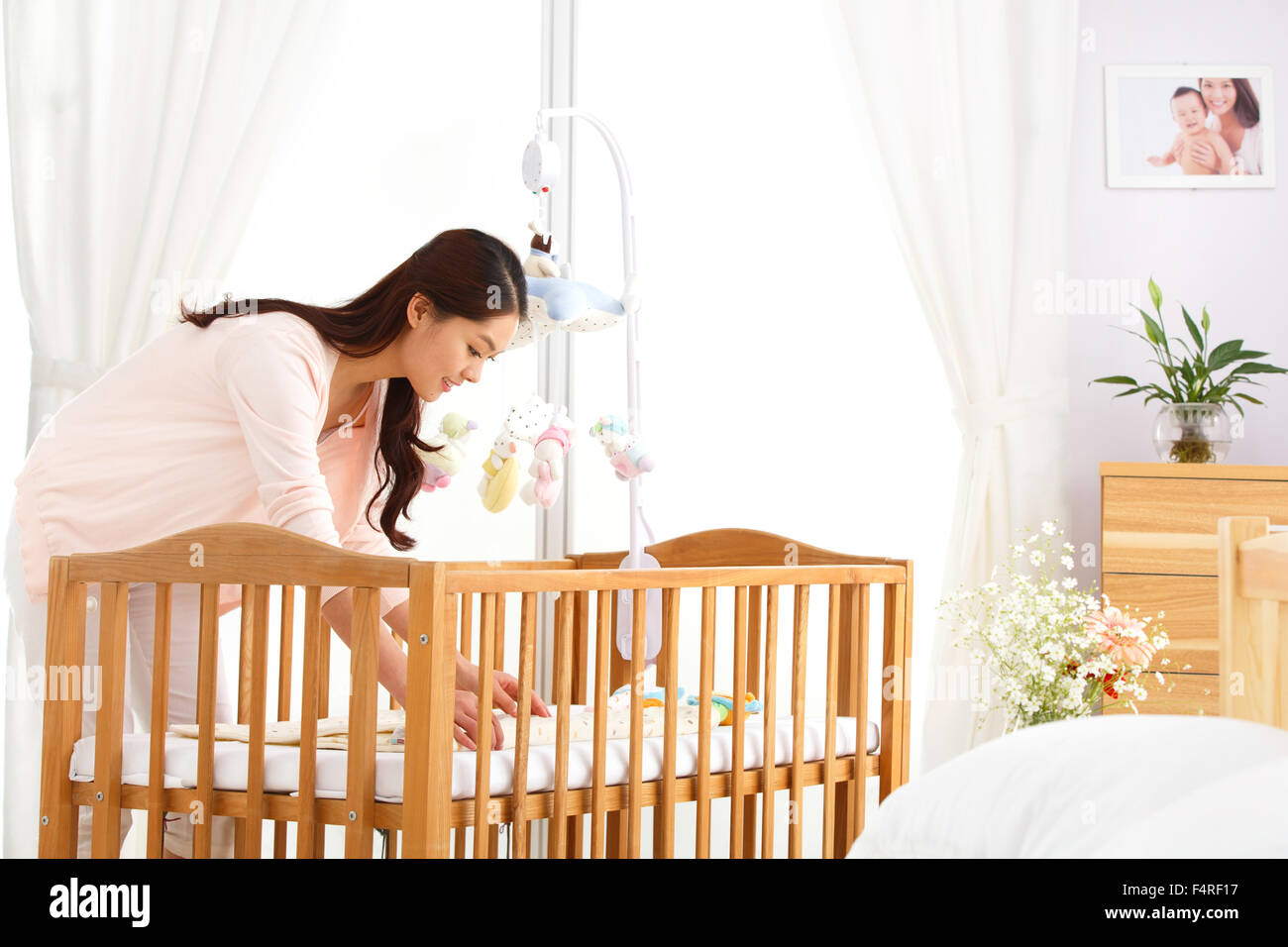 Young mother to organize baby clothes - Stock Image