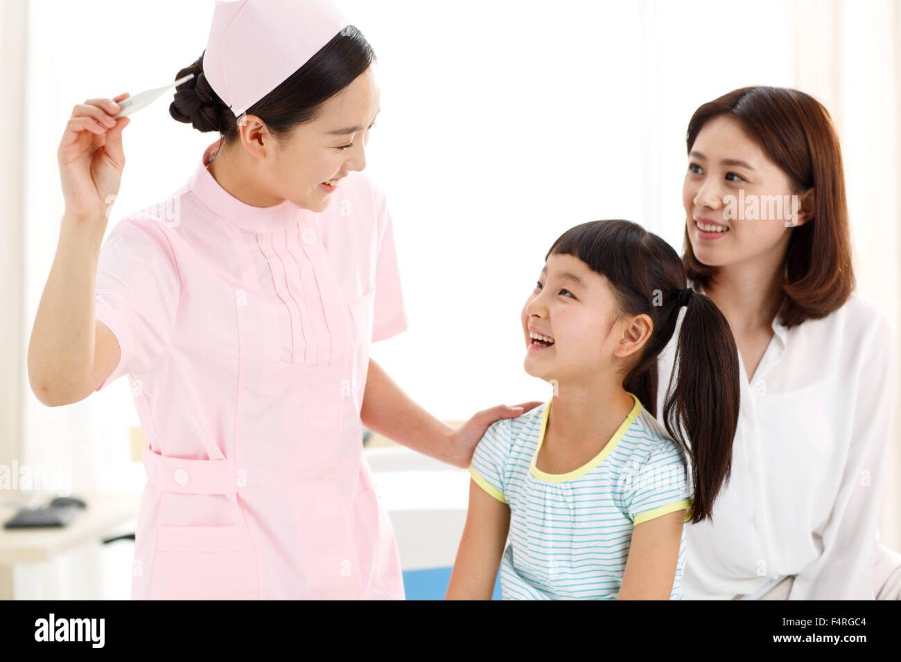The female nurse is giving the little girl the temperature. - Stock Image